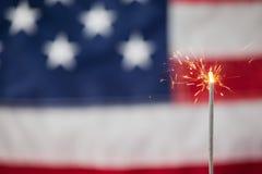 Бенгальские огни горя против предпосылки американского флага стоковые фотографии rf