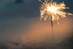 Бенгальский огонь в снеге в вечере Стоковое Изображение