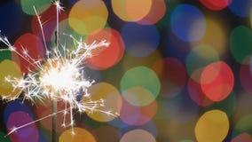 Бенгальский огонь над предпосылкой рождества с запачканным цветом освещает HD Красивая сцена праздника видеоматериал