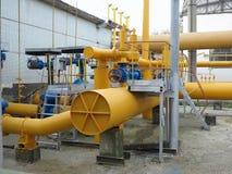 Бензозаправочная станчия природного газа с желтым цветом пускает электростанцию по трубам Стоковое Изображение RF