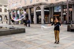 БЕРГЕН, НОРВЕГИЯ - ОКОЛО 2016: Женский уличный исполнитель создает большие пузыри в главным образом городской площади Бергена Стоковые Фотографии RF