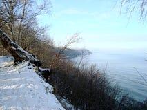 Берег Балтийского моря в зиме, крутом снижении к воде против голубого неба стоковые фото