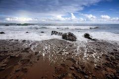 Берег моря с волнами, камнями и небом стоковые изображения rf