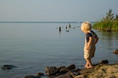 Берег озера при младенец играя с песком, Uveldy ‹ÑŒÐ'Ñ ² УРÐΜл, Уралом стоковая фотография