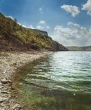 Берег озера с лесом под небом Стоковые Фото
