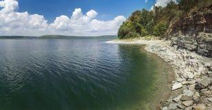 Берег озера с лесом под небом Стоковые Изображения