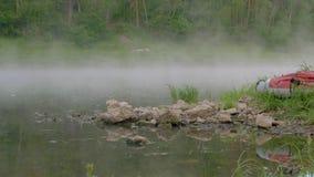 Берег озера с коричневыми камнями и красная шлюпка спокойной водой видеоматериал