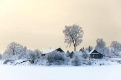 Берег озера с домами тимберса на сезоне зимы с небом захода солнца Стоковая Фотография