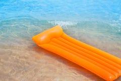 Берег пляжа с померанцовыми плавая салоном и волнами Стоковая Фотография RF