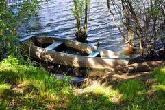 Берег реки с шлюпкой на воде Стоковые Фотографии RF