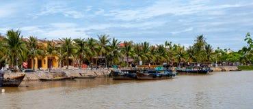 Берег реки берег реки Bon Thu в Hoi, Вьетнаме, с людьми идя вдоль его в дневном времени стоковые изображения rf