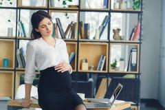 Беременная бизнес-леди работая на боли живота материнства офиса стоковые изображения rf