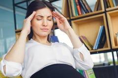 Беременная бизнес-леди работая на головной боли материнства офиса сидя стоковая фотография rf