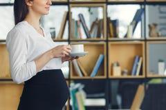 Беременная бизнес-леди работая на кофе материнства офиса стоя выпивая стоковая фотография