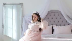 Беременная девушка в розовом платье видеоматериал