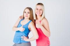 Беременная девушка и ее друг приниманнсяый за фитнес Стоковое фото RF