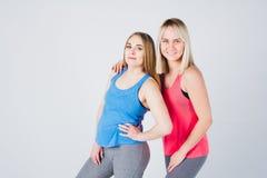 Беременная девушка и ее друг приниманнсяый за фитнес Стоковая Фотография