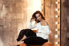 Беременная европейская женщина в белой блузке и черных брюках сидит на стуле в темная плоской, стильный и счастливый стоковые фотографии rf