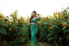 Беременная европейская женщина в поле солнцецветов, красивая молодая европейская женщина ждать ребенка, prenant женщины с стоковые фото