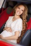 Беременная девушка брюнет и ее красный автомобиль Стоковые Фото