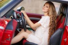 Беременная девушка брюнет и ее красный автомобиль Стоковые Фотографии RF