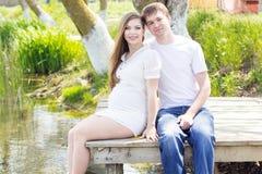 Беременная девушка с супругом сидит на мосте Стоковое Фото