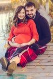 Беременная жена и супруг отдыхают около озера Стоковая Фотография