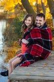 Беременная жена и супруг отдыхают около озера Стоковое фото RF