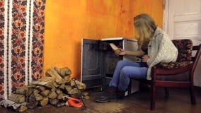 Беременная женщина ласкает ее живот около сельской горящей плиты сток-видео