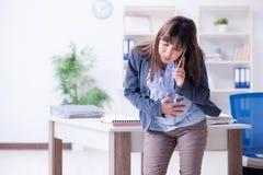 Беременная женщина борясь для того чтобы сделать работу в офисе стоковая фотография rf