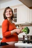 Беременная женщина варя брокколи Стоковое Фото
