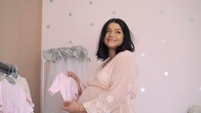 Беременная женщина восхищая младенца одевает в нежной будущей комнате младенца 4K акции видеоматериалы