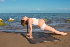 Беременная женщина в бюстгальтере спортов делая тренировку на представлении йоги на море стоковая фотография
