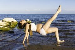 Беременная женщина в бюстгальтере спорт делая тренировку в релаксации на представлении йоги Стоковые Фотографии RF