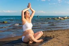 Беременная женщина в бюстгальтере спорт делая тренировку в релаксации на представлении йоги Стоковые Фото