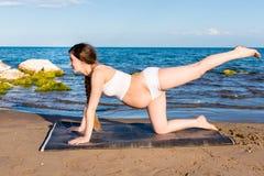 Беременная женщина в бюстгальтере спорт делая тренировку на представлении йоги на море Стоковые Изображения RF