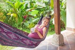 Беременная женщина в гамаке Стоковые Изображения RF