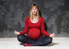 Беременная женщина в красной куртке делая йогу стоковое изображение rf