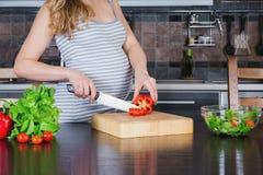 Беременная женщина в кухне варит vegetable салат Стоковые Фотографии RF