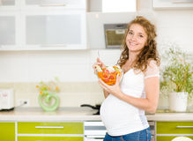 Беременная женщина в кухне Стоковые Изображения RF