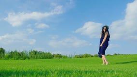 Беременная женщина в светлом платье имея потеху и имея потеху на зеленом луге сток-видео