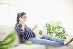 Беременная женщина говоря на ее мобильном телефоне и используя тетрадь Стоковая Фотография