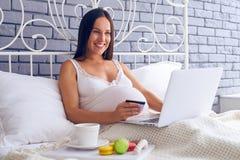 Беременная женщина делая онлайн покупки в спальне Стоковое Фото