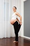 Беременная женщина делая протягивающ тренировку Стоковая Фотография