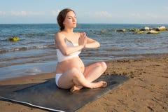 Беременная женщина делая тренировку на представлении йоги на ocea стоковые изображения rf