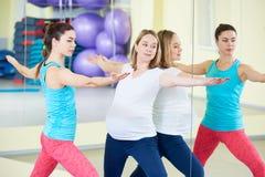 Беременная женщина делая тренировку фитнеса с тренером Стоковое фото RF