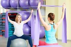 Беременная женщина делая тренировку фитнеса с тренером Стоковые Фото