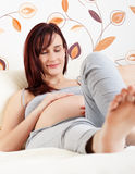 Беременная женщина лежа в кровати Стоковые Изображения