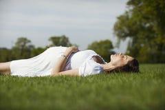 Беременная женщина лежа на траве Стоковое Изображение RF