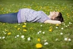 Беременная женщина лежа на траве Стоковые Фото